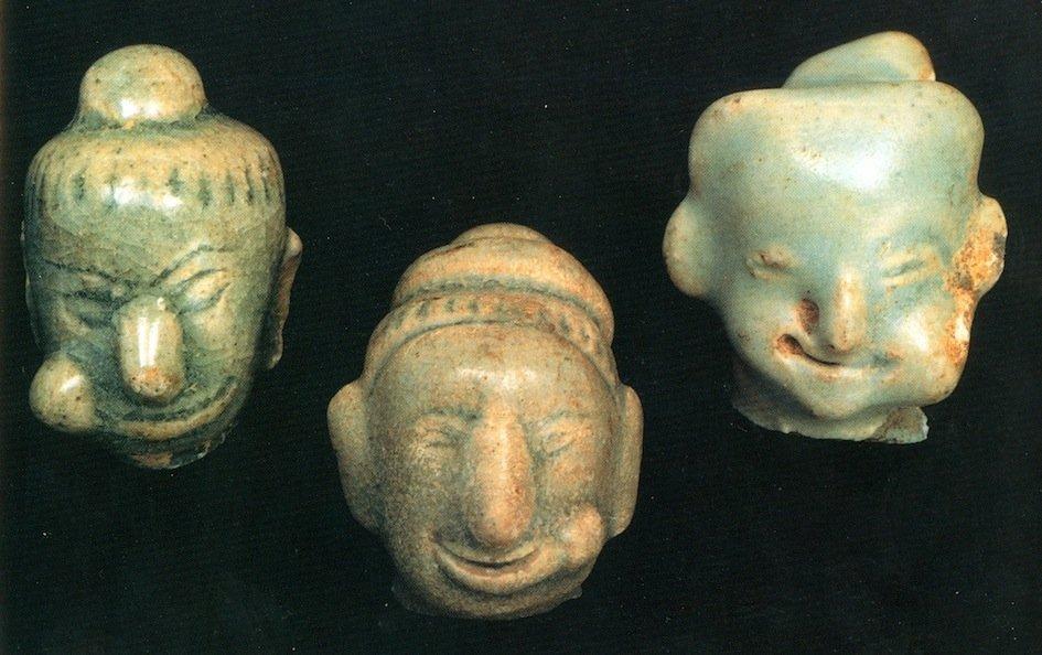 Testine femminili in celadon ritrovati nella regione di Sawankhalok, Tailandia, con evidente raffigurazione sulla guancia del bolo di betel. Altezza 3,5 cm. XIV-XVI secoli d.C. (da Reichart & Philipsen, 2005, tav. 19, p. 33)