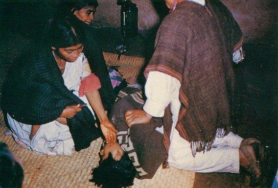 Un momento drammatico in una sessione di cura con i funghi allucinogeni: la curandera María Sabina ha appena saputo dai funghi che il ragazzo malato è destinato a morire e che non c'è possibilità di curarlo, e glielo ha appena comunicato. Il ragazzo si accascia disperato, e María Sabina lo accarezza consolandolo. Il ragazzo effettivamente morì dopo alcuni giorni. Huautla de Jiménez, Oaxaca, Messico, 1958 (da Riedlinger, 1990. tav. 18a)